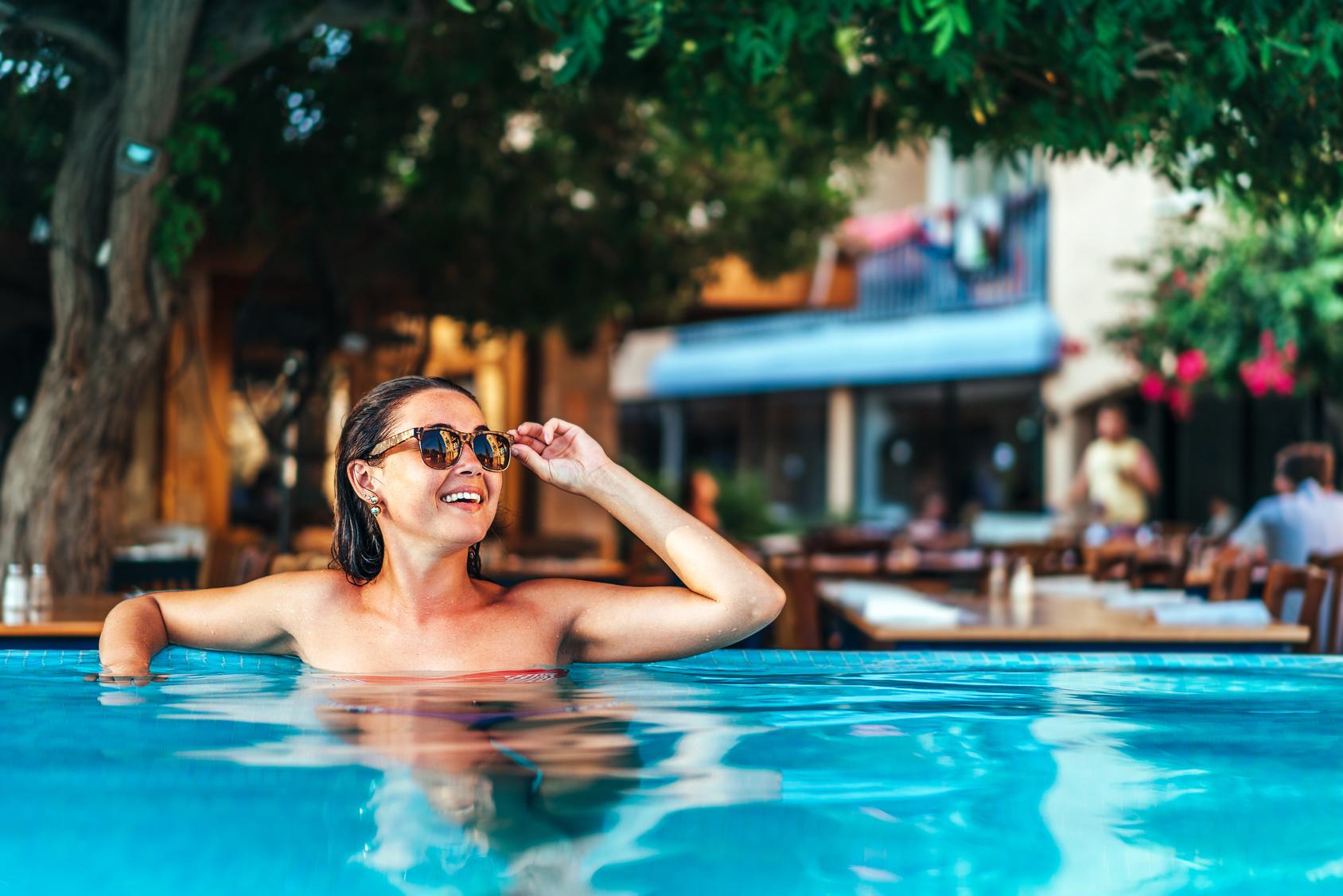 Pretty brunette girl sunbathing at the swimming pool
